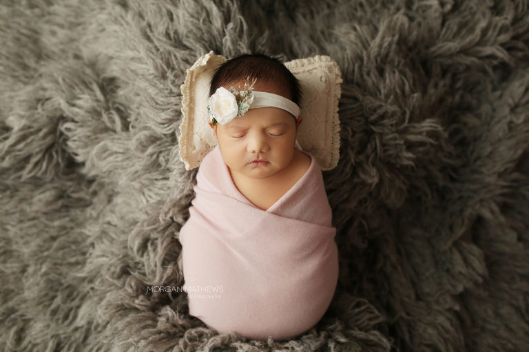 newborn wrapped up and wearing a headband in norther Nevada